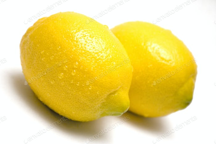 Two Lemons with Water Drops Isolated on a White Background