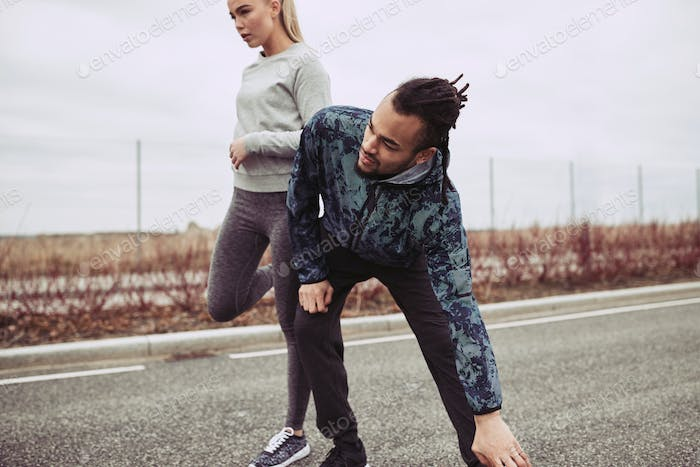Young couple stretching before jogging on a country road