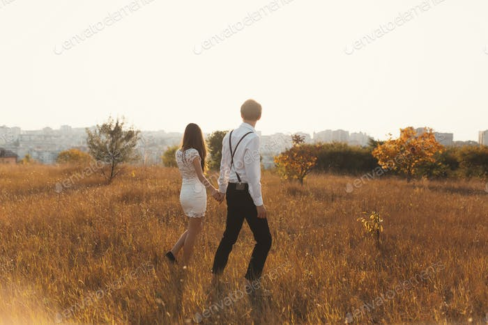 A couple enjoying a walk, holding hands, with the city on the ho