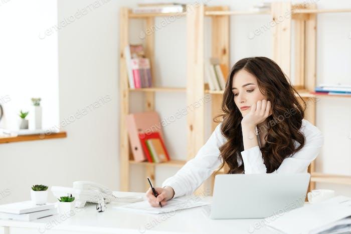 Junge hübsche Geschäftsfrau mit Notizbuch und Dokument im hellen modernen Büro drinnen