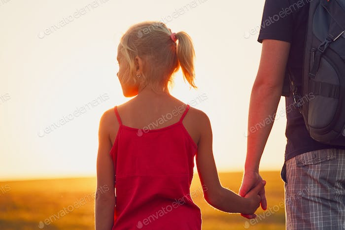 Girl holding hand his father