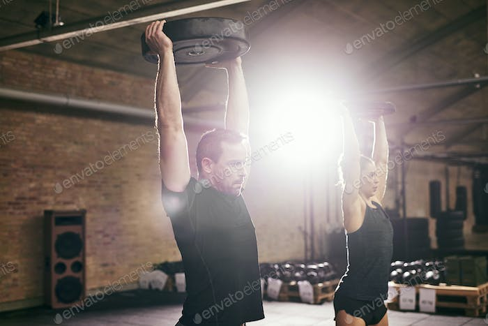 Young athletic adults lifting weights in gym