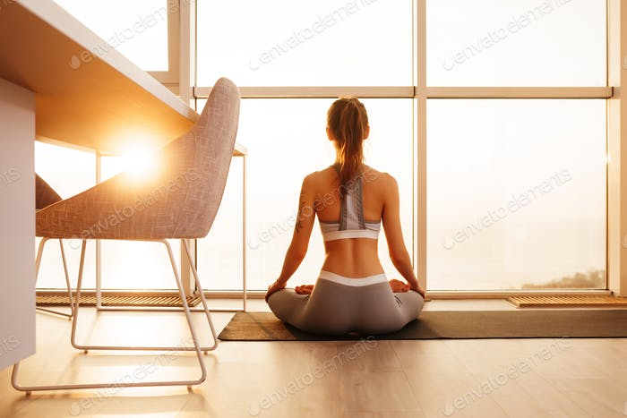 Young beautiful lady sitting in lotus pose on yoga mat and meditating near big windows at home