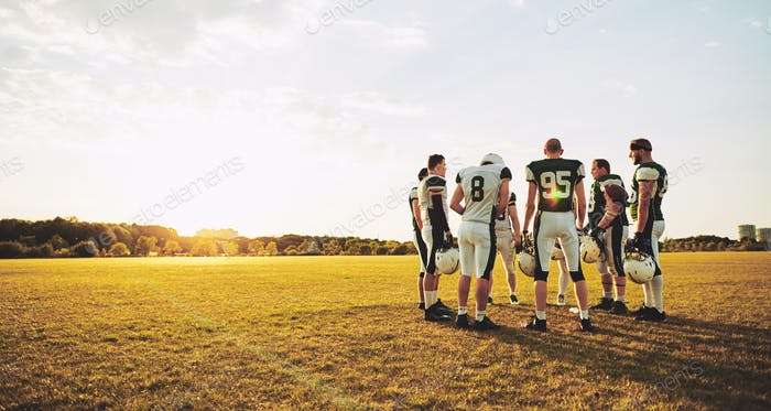 American football players talking together during an afternoon practice