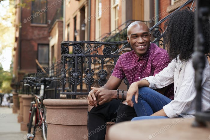 Couple Sit And Talk On Stoop Of Brownstone In New York City Foto Von