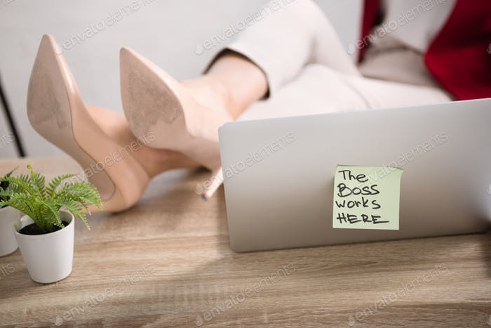 female legs on table near laptop with the boss works here sticker