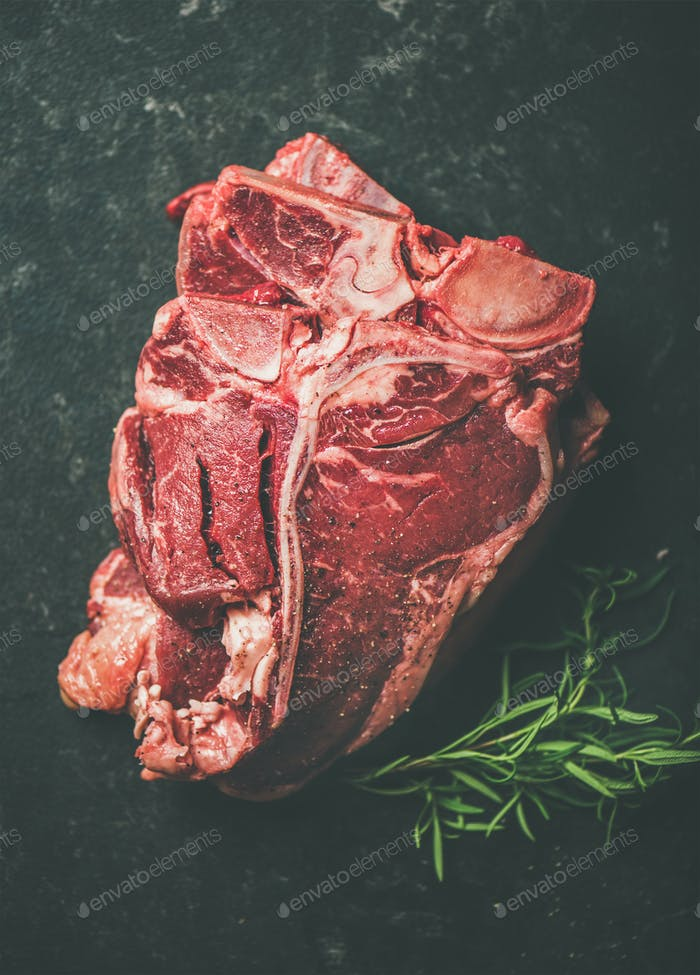 Raw beef meat t-bone steaks with rosemary placed in stack