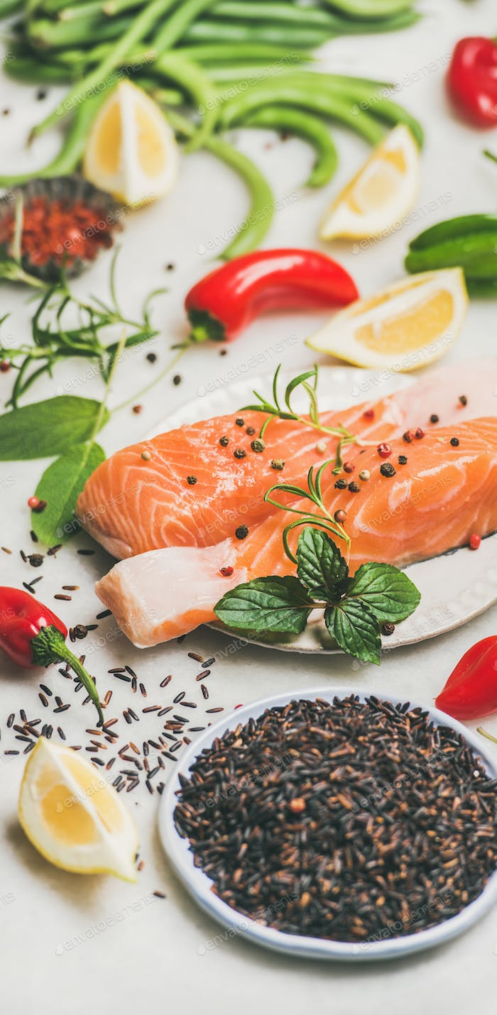 Raw salmon steaks with vegetables, greens and rice, marble background