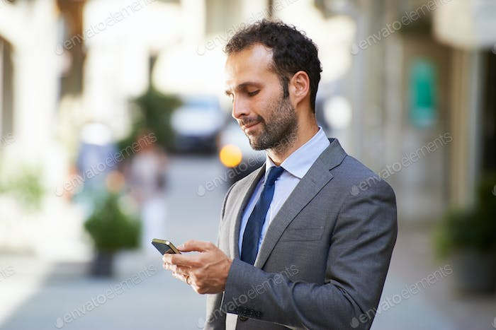 Business Man Typing Sms On Mobile Phone In Street