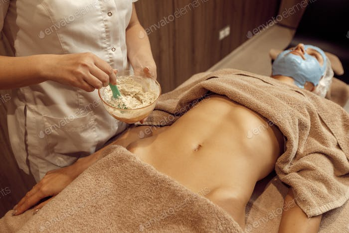 Female masseur applies cream on stomach of woman
