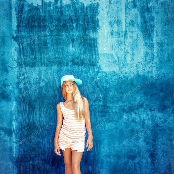 Portrait of a teenage girl in the cap with a blue wall