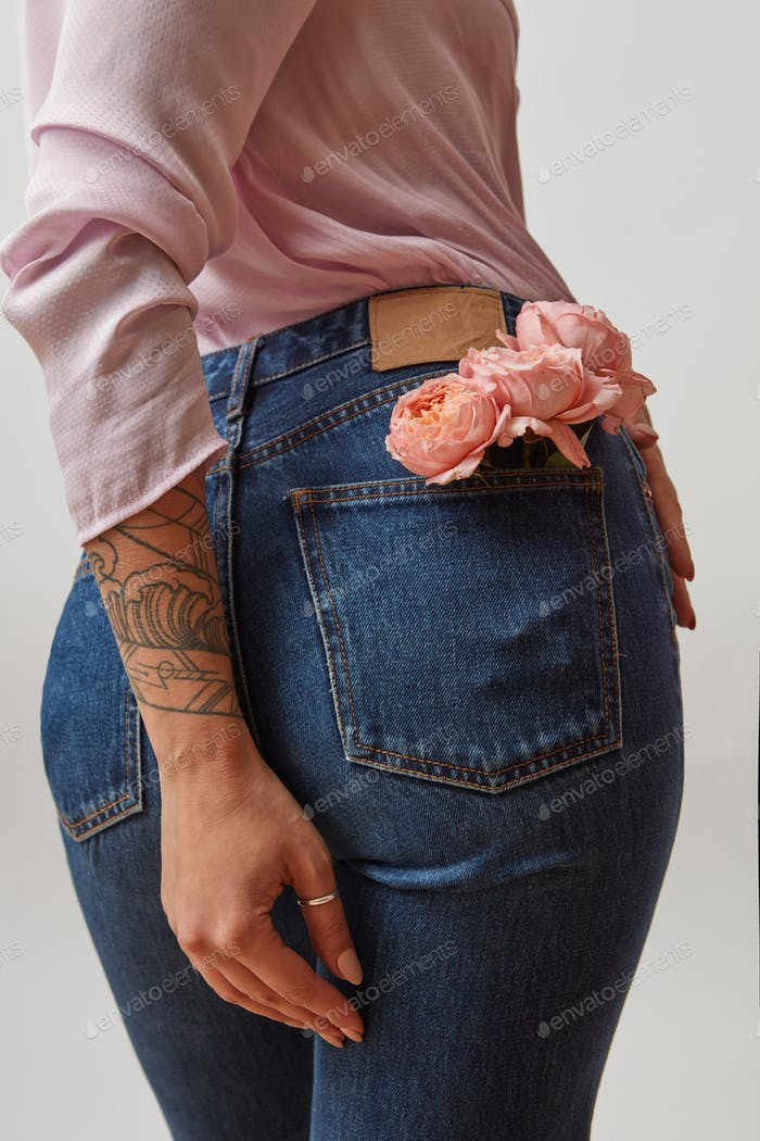 Young pretty woman dressed in blue jeans and pink jacket with fresh roses in a back pocket and her