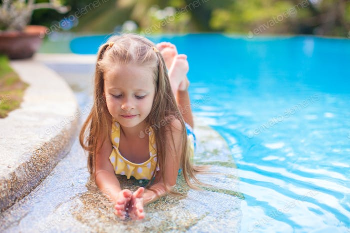 Closeup of Cute little girl in the swimming pool looks at camera
