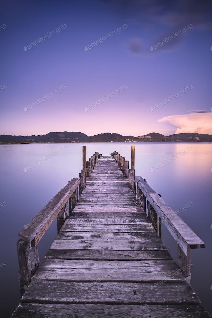 Hölzerner Pier oder Steg auf einem blauen See Sonnenuntergang und Himmel Reflexion auf