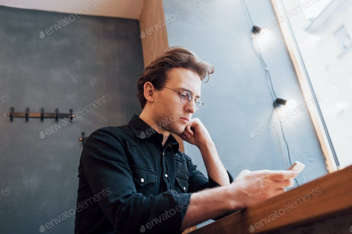soft focus.man holding and using sell phone.while sitting and relax on sofa at modern house.concept