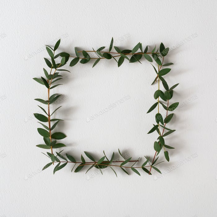 Creative frame arrangement made with green leaves on bright background. Minimal nature
