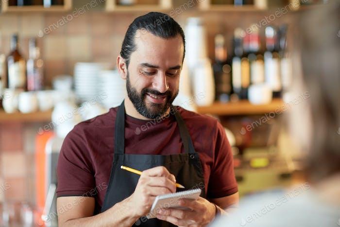 man or waiter serving customer at bar