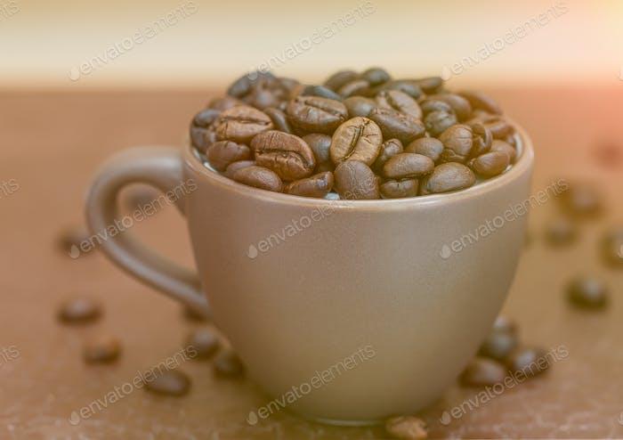 Geröstete Kaffeebohnen in brauner Kaffeetasse