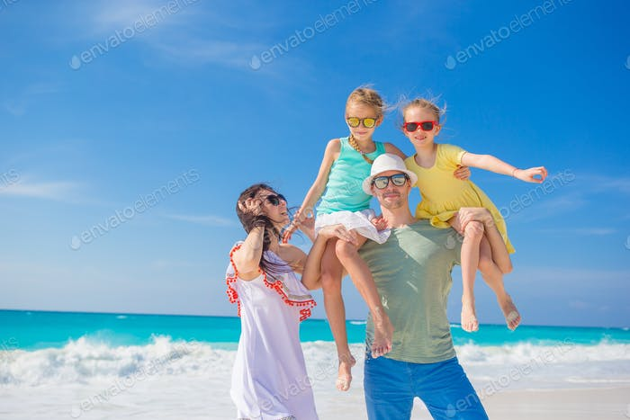 Portrait of happy beautiful family of four on a tropical beach on Carribean vacation