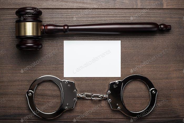 Handschellen und Richter Gavel auf Holzhintergrund