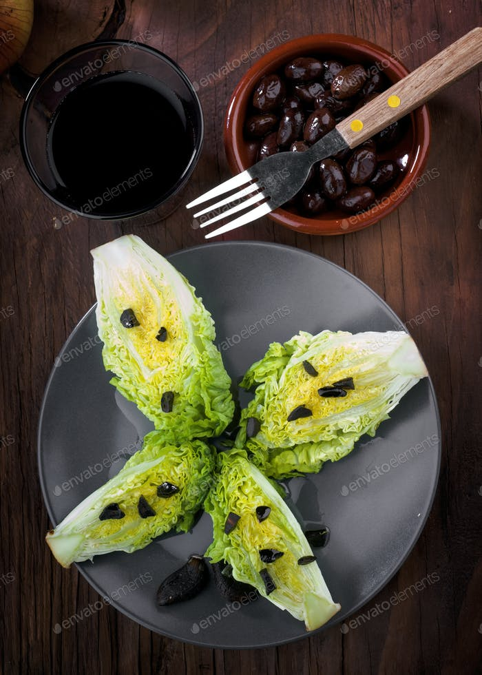 lettuce buds with black garlic on wooden rustic board
