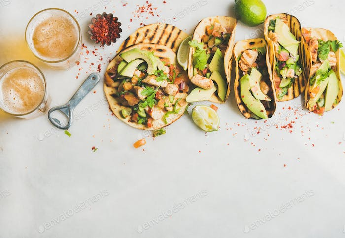 Healthy corn tortillas with grilled chicken, avocado, lime, beer