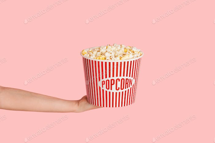 Millennial girl holding bucket of fresh crunchy popcorn over pink background, close up