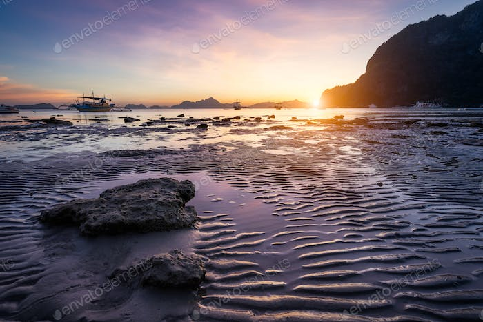 Tropical beach in ebb time low tide on sunset. Mudflats and sun reflections at the golden hour