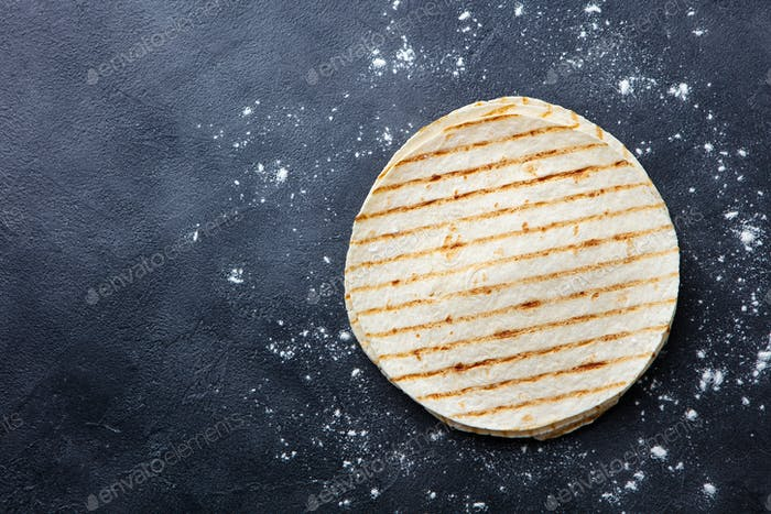 Grilled Tortillas, Flat Breads on Dark Grey Background. Copy space. Top view.
