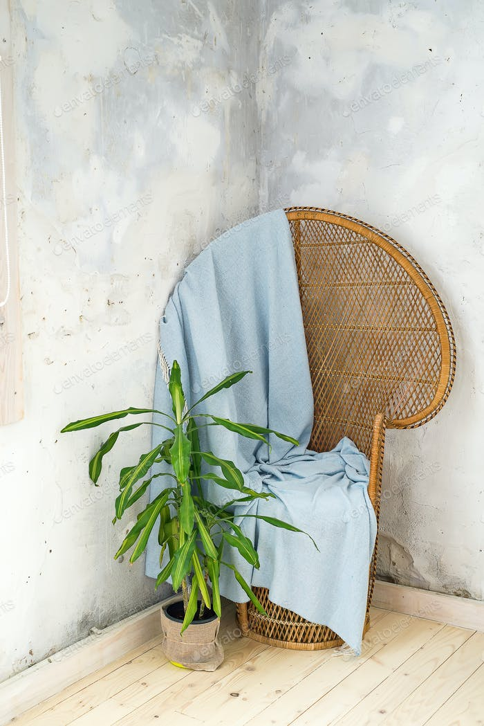 vintage ancient wooden chair with blue plaid knitted for the cover on a light wooden background