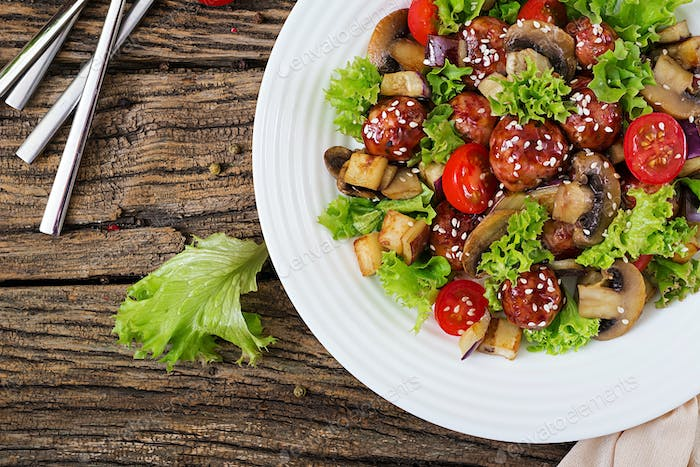 Salad with meatballs, eggplant, mushrooms and tomatoes in Asian style