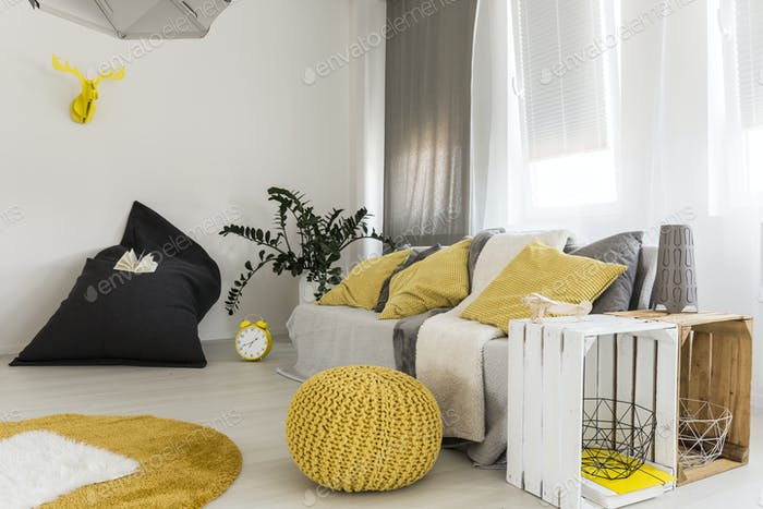 Room with couch and yellow pouf