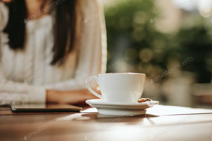 Cup of coffee and digital tablet on cafe table with woman.