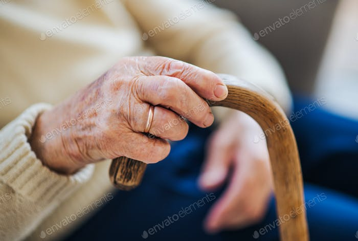 A close-up of a senior woman holding a walking stick at home.