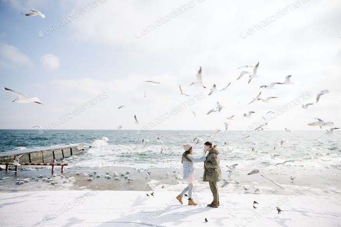 Happy Young Couple Walking on Seashore With Seagulls in Winter