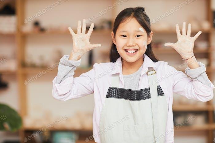 juguetón asiático chica en cerámica clase