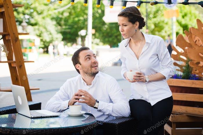 Business-Team Mann und Frau im Cafe mit einem Gespräch mit Laptop. Working Meeting Konzept