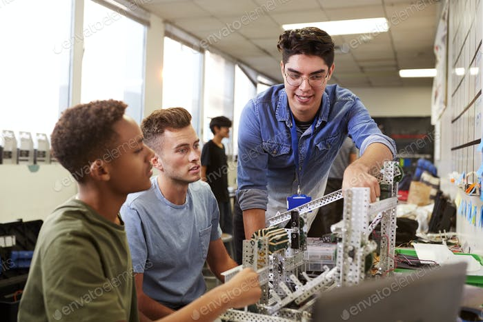 Teacher With Two Male University Students Building Machine In Science Robotics Or Engineering Class