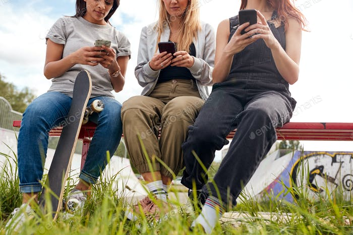Group Of Female Friends With Skateboard Using Mobile Phones In Urban Skate Park