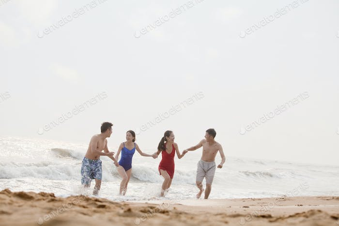 Four friends running out of the water on a sandy beach