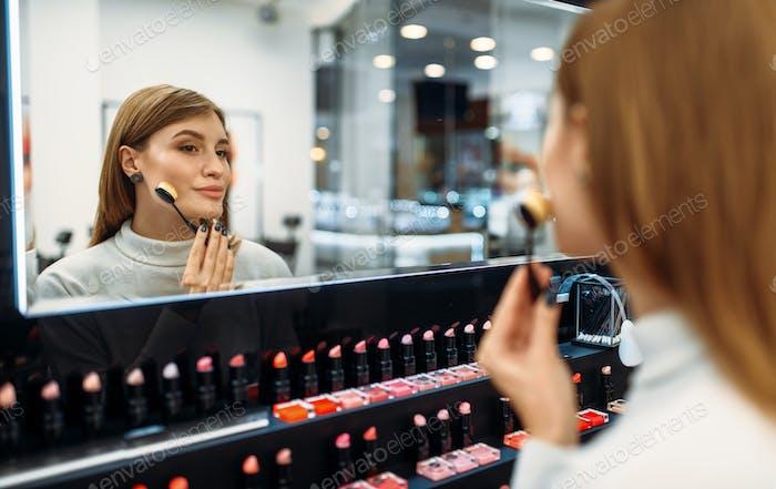 Cliente Mujer mira el espejo en la tienda de maquillaje