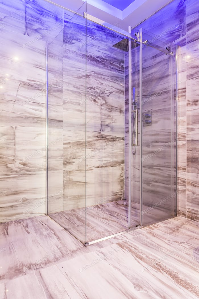Glass shower stall in marble bathroom