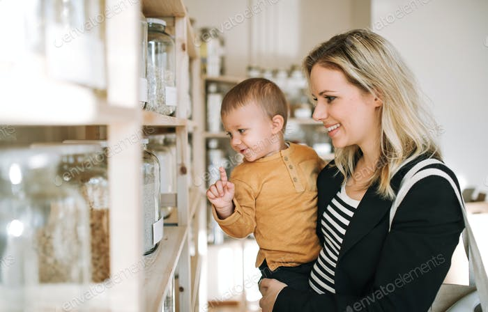 Thumbnail for A young woman with a toddler boy buying groceries in zero waste shop.