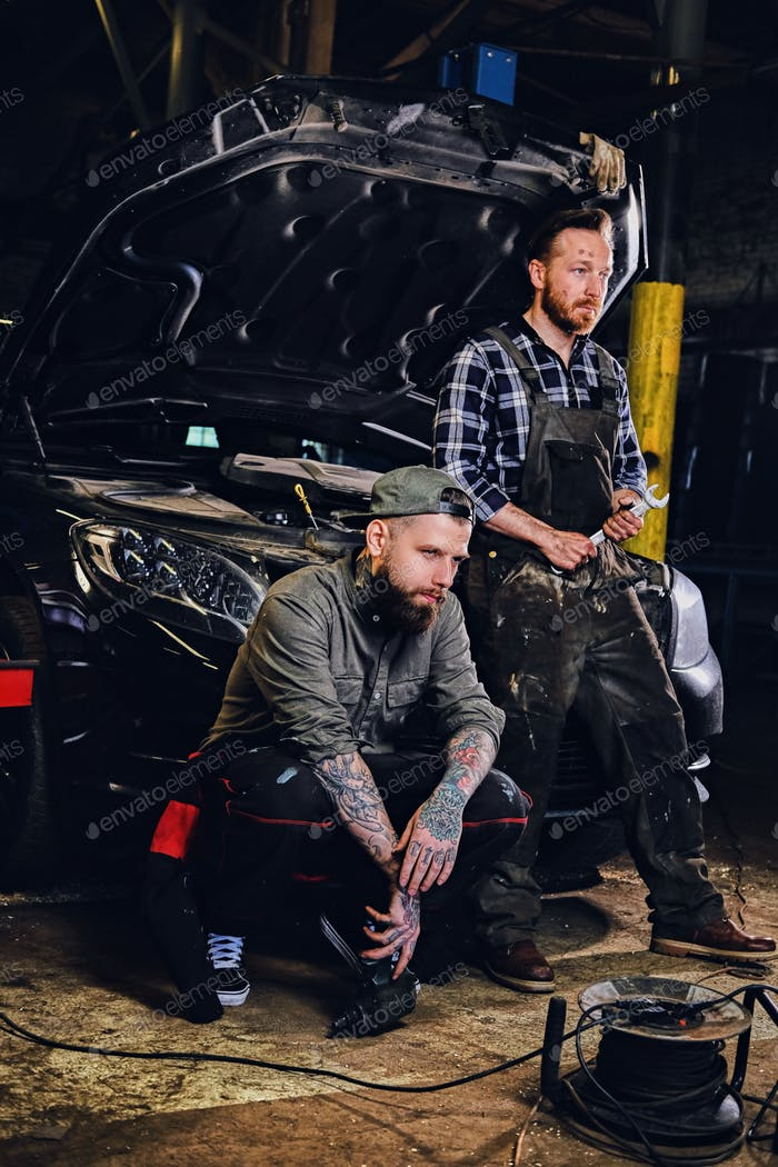 Two bearded tattooed mechanics near the car in a workshop.
