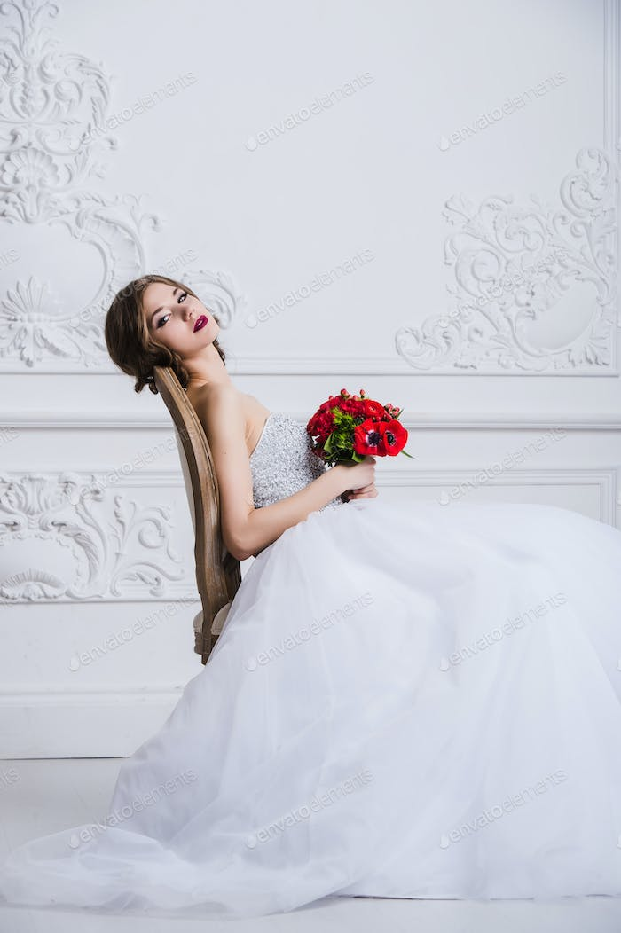Close portrait of beautiful smiling bride woman with long curly hair posing in wedding dress at