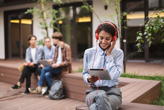 Photo of young lady sitting on bench in red headphones and tablet in hands