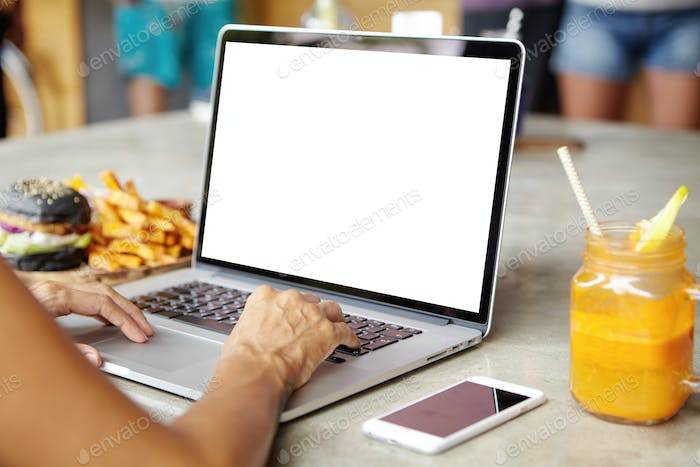 People, technology and leisure concept. Cropped view of woman freelancer sitting at cafe and working