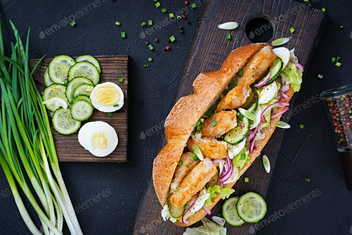 Thumbnail for Baguette sandwich with fish, egg, pickled onions and lettuce leaves. Top view