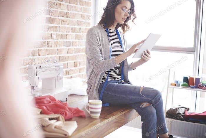 Fashion designer with digital tablet at her studio
