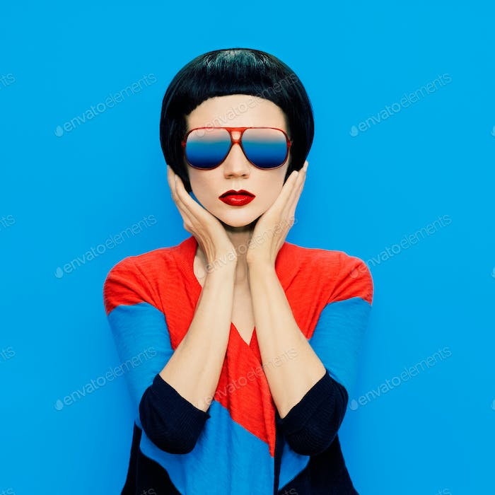brunette lady with fashion haircut and sunglasses on a blue back